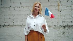 Attraktiv mogen kvinna som vinkar fransk flaggadet fria på bakgrund för tegelstenvägg stock video
