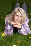 Attraktiv mognad kvinna som ligger i höstgräset Arkivfoton