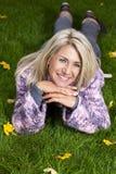 Attraktiv mognad kvinna som ligger i höstgräset Arkivbilder
