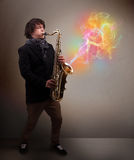 Attraktiv musiker som spelar på saxofonen med färgrikt abstrakt begrepp Royaltyfri Foto