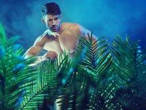 Attraktiv muskulös man i djungeln arkivbilder