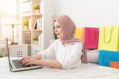 Attraktiv muslimkvinna som använder den mobila bärbara datorn royaltyfri fotografi