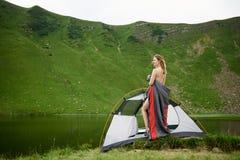 Attraktiv naken kvinna, i att campa fotografering för bildbyråer