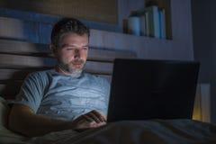 Attraktiv och avkopplad nätverkande för internetknarkareman som sent koncentreras på natten på säng med bärbar datordatoren i soc royaltyfria foton