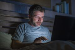 Attraktiv och avkopplad nätverkande för internetknarkareman som sent koncentreras på natten på säng med bärbar datordatoren i soc royaltyfria bilder
