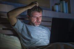 Attraktiv och avkopplad nätverkande för internetknarkareman som sent koncentreras på natten på säng med bärbar datordatoren i soc arkivfoton