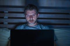 Attraktiv och avkopplad nätverkande för internetknarkareman som sent koncentreras på natten på säng med bärbar datordatoren i soc arkivbilder