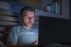Attraktiv och avkopplad nätverkande för internetknarkareman som sent koncentreras på natten på säng med bärbar datordatoren i soc royaltyfri foto