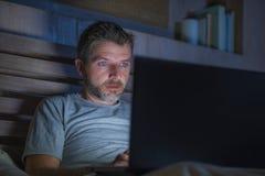 Attraktiv och avkopplad nätverkande för internetknarkareman som sent koncentreras på natten på säng med bärbar datordatoren i soc royaltyfri bild