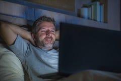 Attraktiv och avkopplad nätverkande för internetknarkareman som sent koncentreras på natten på säng med bärbar datordatoren i soc arkivfoto