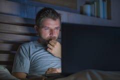 Attraktiv och avkopplad nätverkande för internetknarkareman som sent koncentreras på natten på säng med bärbar datordatoren i soc fotografering för bildbyråer