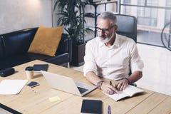 Attraktiv och förtrolig vuxen affärsman som använder den mobila bärbar datordatoren och gör anmärkningar, medan arbeta på det trä Arkivbild