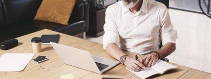 Attraktiv och förtrolig vuxen affärsman som använder den mobila bärbar datordatoren och gör anmärkningar, medan arbeta på det trä Royaltyfria Foton