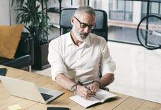 Attraktiv och förtrolig vuxen affärsman som använder den mobila bärbar datordatoren, medan arbeta på trätabellen på modernt Arkivfoton