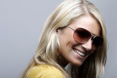 Attraktiv och gladlynt kvinnlig modell i solglasögon royaltyfria foton