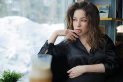 Attraktiv och gladlynt ung kvinna som ler i kaf? arkivfoton