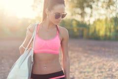 Attraktiv passformkvinna i sportswearutbildning utomhus, kvinnlig idrottsman nen med den perfekta kroppen som vilar efter genomkö Arkivfoton