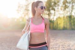 Attraktiv passformkvinna i sportswearutbildning utomhus, kvinnlig idrottsman nen med den perfekta kroppen som vilar efter genomkö Arkivfoto
