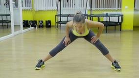 Attraktiv passformkvinna som övar i studio med copyspace Bild av den sunda unga kvinnliga idrottsman nen som gör konditiongenomkö lager videofilmer