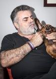 Attraktiv pensionär med det vita skägget som spelar med taxhunden Royaltyfria Bilder