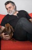 Attraktiv pensionär med det vita skägget som spelar med taxhunden Arkivfoto