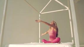 Attraktiv praktiserande yoga för ung kvinna i säng stock video