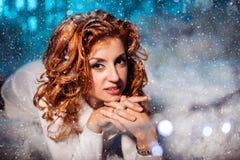 Attraktiv röd kvinnlig elevrepresentant som knäfaller på alla fyrana bland snödrivan royaltyfria foton
