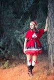 Attraktiv röd ridninghuv i skogen Royaltyfri Bild