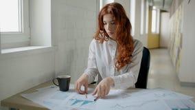 Attraktiv rödhårig mankvinna som arbetar med ritningen som sitter på tabellen i modernt ljust kontor lager videofilmer