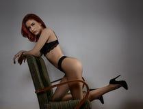 Attraktiv röd hårmodell med svart damunderkläder som provocatively sitter på stol, grå bakgrund sinnlig kvinna för modestående Arkivbilder