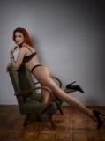Attraktiv röd hårmodell med svart damunderkläder som provocatively sitter på stol, grå bakgrund sinnlig kvinna för modestående Royaltyfri Foto