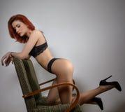 Attraktiv röd hårmodell med svart damunderkläder som provocatively sitter på stol, grå bakgrund sinnlig kvinna för modestående Royaltyfri Fotografi