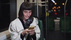 Attraktiv ridning för ung kvinna i kollektivtrafiken genom att använda smartphonen Hon är att smsa som kontrollerar poster, prats arkivfilmer