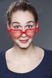 Attraktiv rolig 20-talkvinna med förälskelseexponeringsglas på hennes näsa Royaltyfri Bild