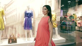 Attraktiv säker roterande runda för ung kvinna, medan promenera beklär diversehandel arkivfilmer