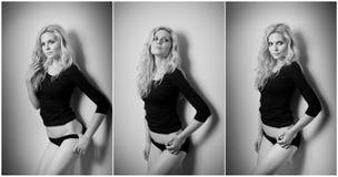 Attraktiv sexig blondin i svart åtsittande den passformblus och bikinin som provocatively poserar Stående av den sinnliga kvinnan Arkivbild