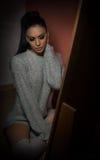 Attraktiv sexig brunett i den vita bekväma sweatern som inomhus poserar Stående av sinnligt dagdrömma för ung kvinna Royaltyfria Bilder