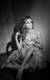 Attraktiv sexig ung kvinna som slås in i ett sammanträde för pälslag i hotellrum Svartvit stående av sinnligt kvinnligt dagdrömma Arkivfoto