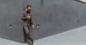 Attraktiv skäggig affärsman som omkring ser och använder hans smartphone, medan bli ut ur den moderna byggnaden,