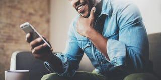Attraktiv skäggig afrikansk affärsman som använder smartphonen, medan sitta på soffan på hans hem Begrepp av ungdomar royaltyfria foton