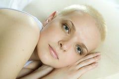 attraktiv skallig blond liggande fundersam kvinna Arkivbild