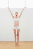 Attraktiv slank kvinna som sträcker lyfta henne armar som ser kameran Arkivbilder