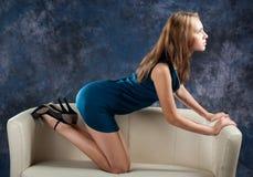 Attraktiv spenslig flicka på henne knä på soffan Royaltyfri Fotografi