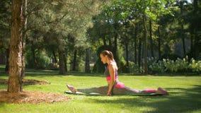 Attraktiv sportig kvinna som utomhus gör splittringar stock video