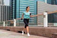 Attraktiv sportig spring för ung kvinna på trottoar royaltyfri foto
