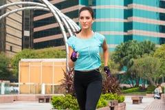 Attraktiv sportig spring för ung kvinna på trottoar arkivbilder