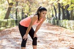 Attraktiv sportkvinna i löparesportswearandning som kippar och tar ett avbrott som tröttas och evakueras efter rinnande genomköra royaltyfri bild