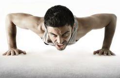 Attraktiv sportmanutbildning skjuter upp övningen som isoleras på vit Royaltyfri Fotografi