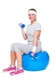 Attraktiv sportswoman som gör övningen för biceps Fotografering för Bildbyråer