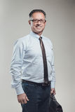 Attraktiv stående för affärsman på grå bakgrund Fotografering för Bildbyråer